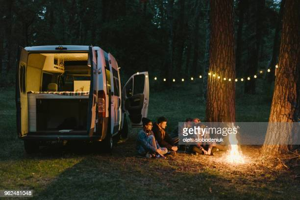 friends camping near the forest - campfire stock pictures, royalty-free photos & images
