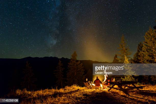friends camping on mountain against star field at night - campfire stock pictures, royalty-free photos & images