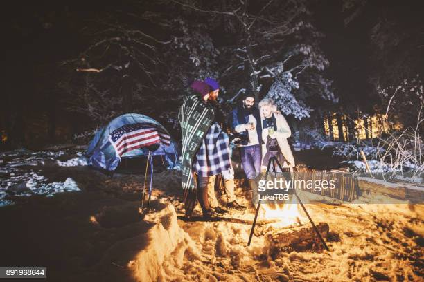 Friends camping on snowy mountain