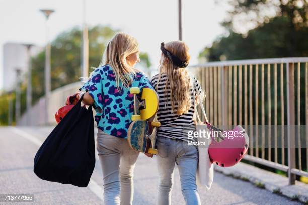 Friends carrying skateboards while walking by railing on sunny day