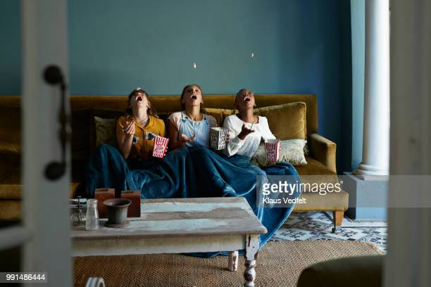3 friends catching popcorn with the mouth - sofa stock-fotos und bilder