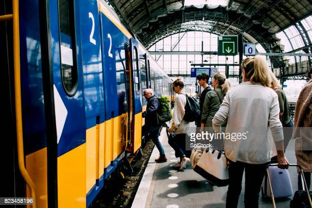 friends catching the train in amsterdam - railway station stock pictures, royalty-free photos & images