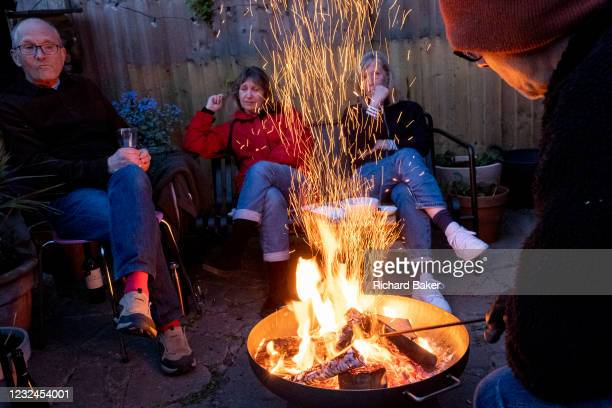 Friends catch-up with latest news and gossip while gathered around the warmt flames of a circluar fire bowl that hosts have lit in their south London...