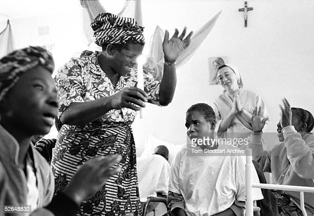 Friends celebrate the baptism of AIDS sufferer Janet Muleya at the Mother of Mercy Hospice Chilanga Zambia It is estimated that 254 million people...