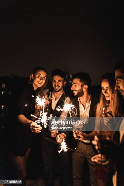 friends celebrate the new year on the rooftop - happy new year 2020 stock photos and pictures
