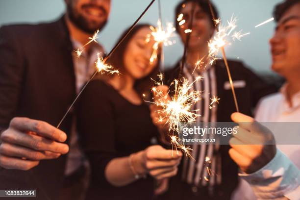 friends celebrate the new year on the rooftop - new year's eve stock pictures, royalty-free photos & images
