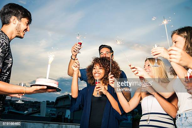 Friends celebrating a birthday party on a rooftop