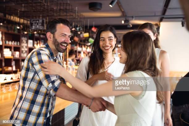 vrienden vieren een feestje in een café - begroeten stockfoto's en -beelden
