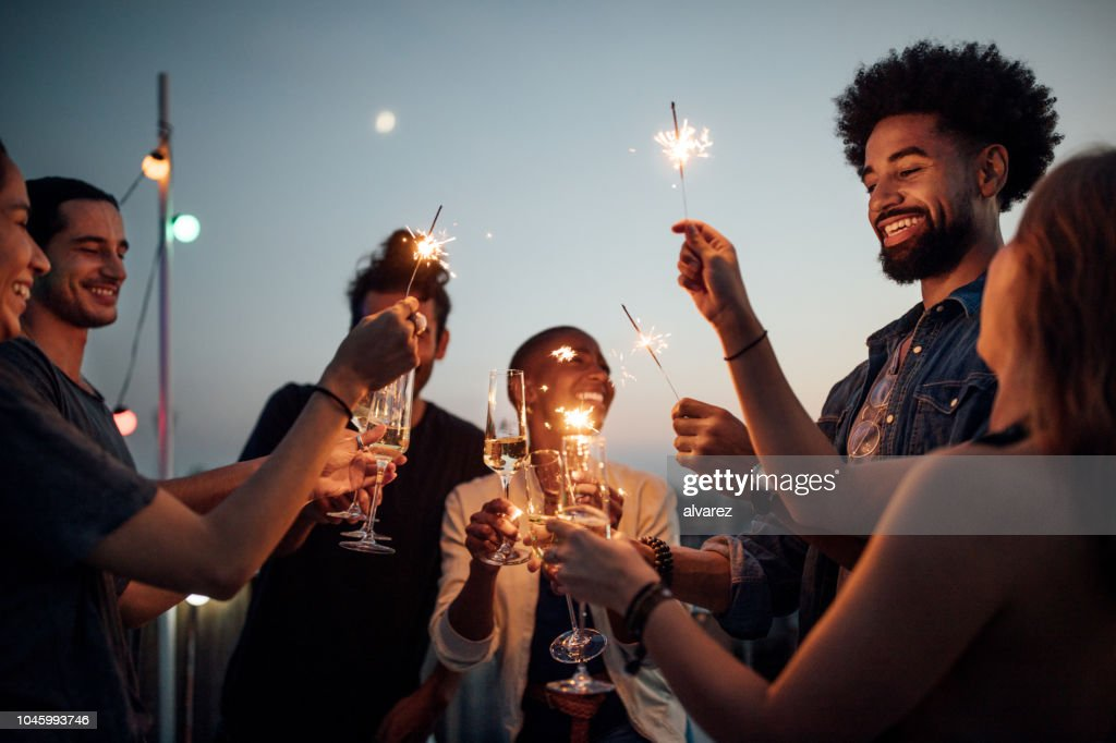 Friends celebrating at party on rooftop : Stock Photo