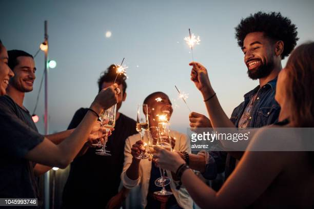 friends celebrating at party on rooftop - roof stock pictures, royalty-free photos & images