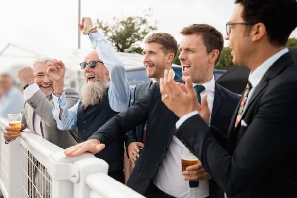 amis de célébrer aux courses - course hippique photos et images de collection