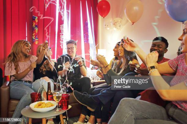 friends celebrating birthday at house party - party social event stock pictures, royalty-free photos & images