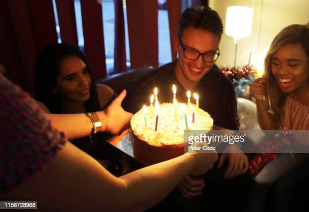 friends celebrating birthday at house party - birthday cake stock pictures, royalty-free photos & images