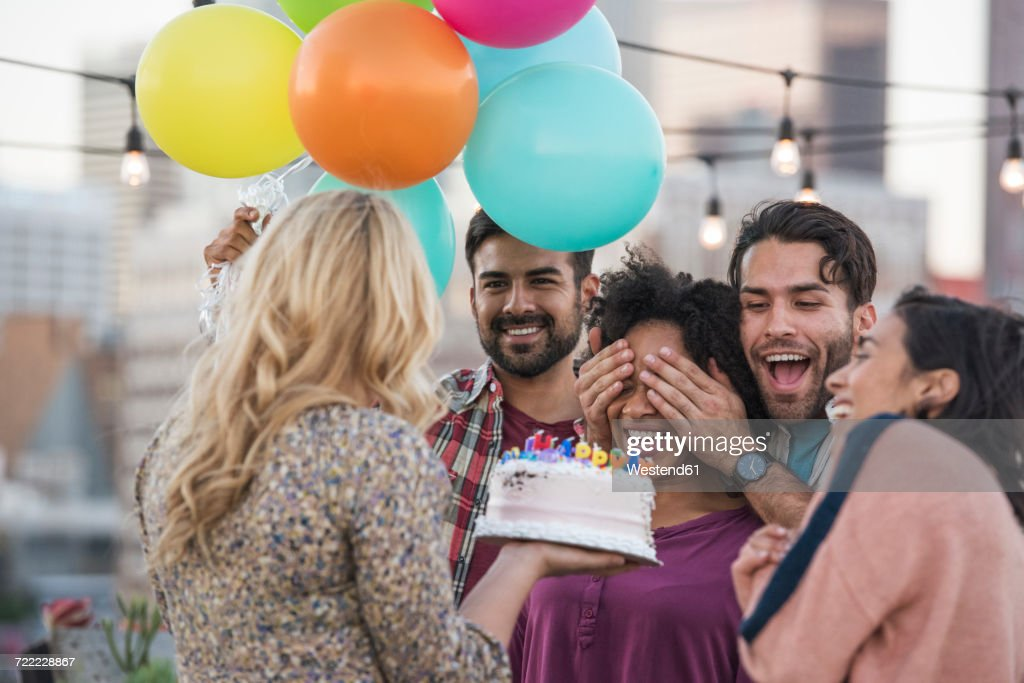 Friends celebrating birthday party on rooftop with birthday cake : Stock Photo