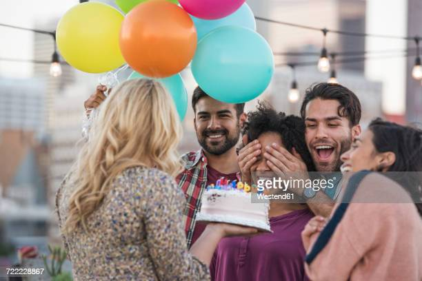Friends celebrating birthday party on rooftop with birthday cake