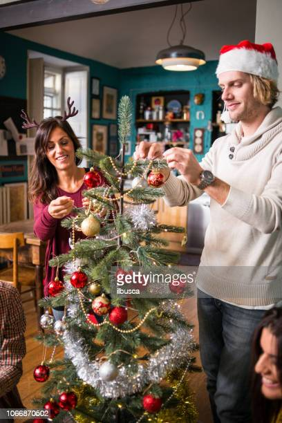Friends celebrating Christmas: Preparing the Christmas tree