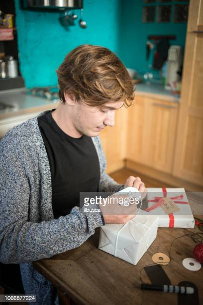 Friends celebrating Christmas: Young man preparing the Christmas presents