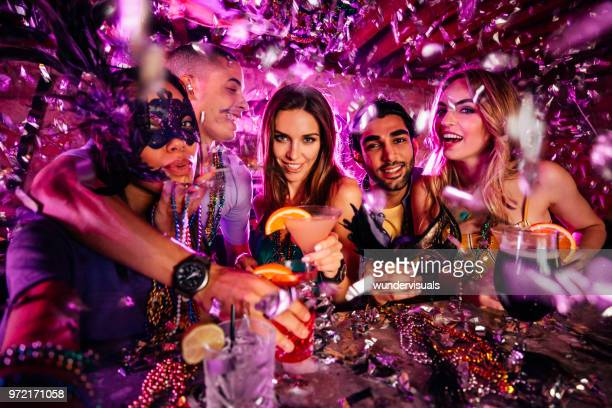 Friends celebrating Mardi Gras and taking selfies at night club