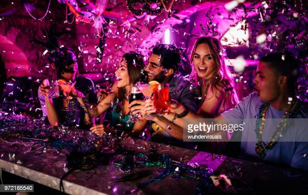 friends celebrating mardi gras with drinks at night club - new orleans french quarter stock photos and pictures