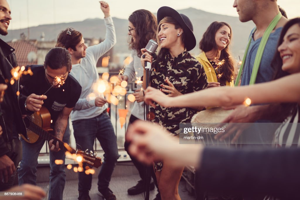 Friends celebrating New Year on rooftop party : Stock Photo