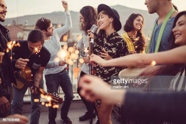 friends celebrating new year on rooftop party - singing stock pictures, royalty-free photos & images