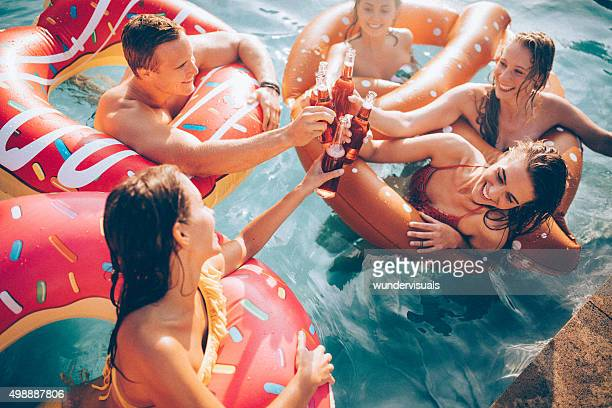 Friends celebrating summer in a pool with bottled beverages