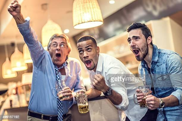 Amis célébrant leur équipe de marquer dans un bar