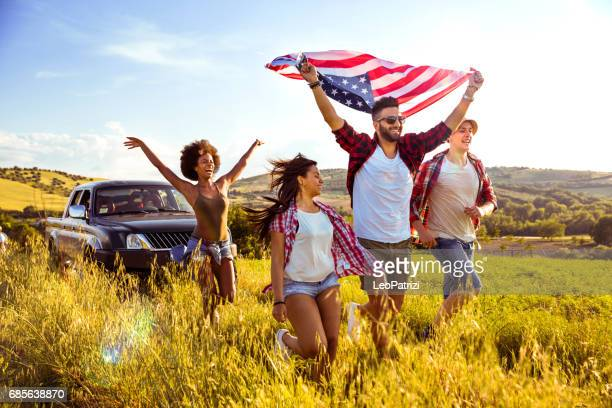 Friends celebrating together holding a US flag on field