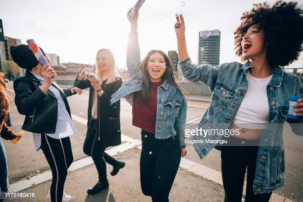friends celebrating with confetti and soap bubbles in street, milan, italy - denim jacket stock pictures, royalty-free photos & images