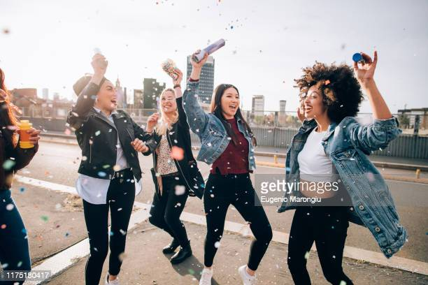 friends celebrating with confetti and soap bubbles in street, milan, italy - generation z stock pictures, royalty-free photos & images