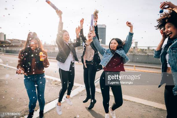 friends celebrating with confetti and soap bubbles in street, milan, italy - excitation photos et images de collection