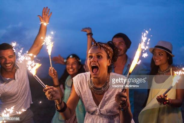 Friends celebrating with fireworks on beach at night