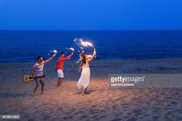 Friends celebrating with flaming torches on beach