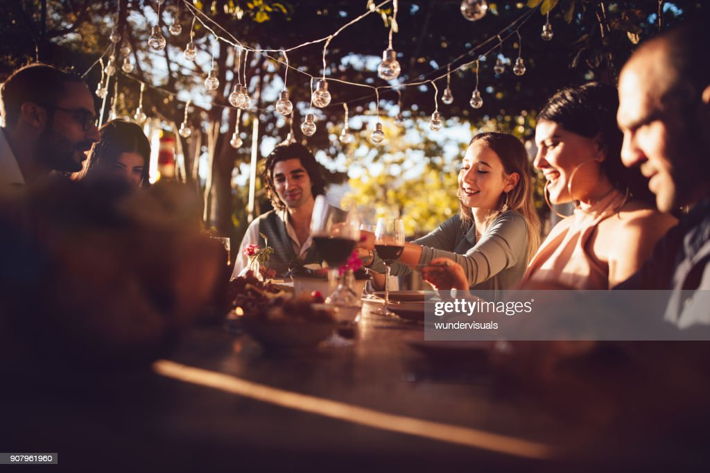 Friends celebrating with wine and food at rustic countryside party : Foto de stock