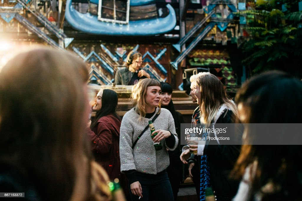 Friends Chatting And Drinking At Club Together : Stock Photo