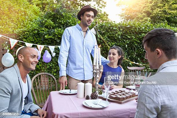 Friends chatting around table at garden party