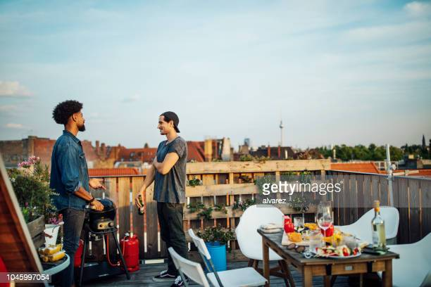 friends chatting at barbecue party on rooftop - building terrace stock pictures, royalty-free photos & images