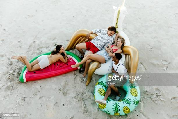 Friends chatting on inflatable toys on the beach
