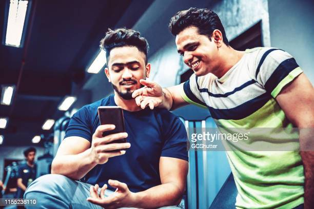 friends checking out the social media feed at a gym - masculinity stock pictures, royalty-free photos & images