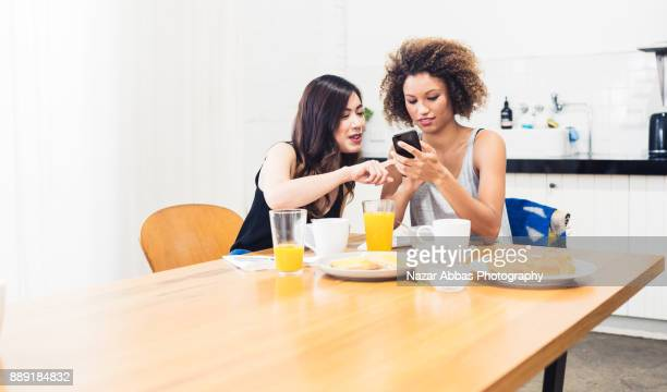 Friends checking phone while having breakfast.