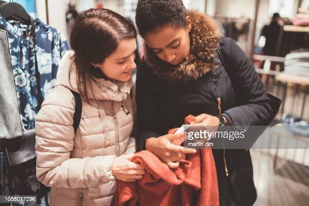 freunde, die überprüfung der preis in dem bekleidungsgeschäft - preisschild stock-fotos und bilder