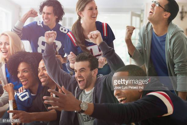 Friends cheering at game on television