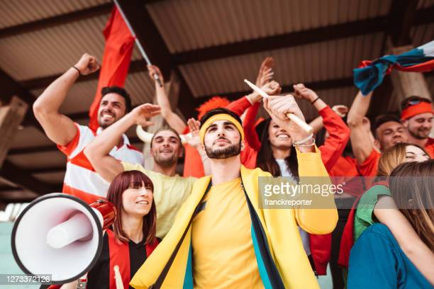 friends cheering at the stadium with megaphone - international soccer event stock pictures, royalty-free photos & images