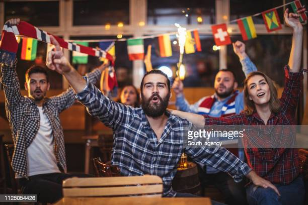 friends cheering for their sports team at the pub - international multi sport event stock pictures, royalty-free photos & images