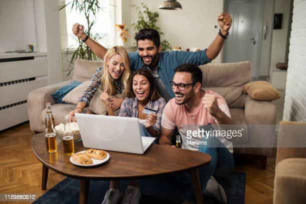 friends cheering for their team and betting online - charging sports stock pictures, royalty-free photos & images