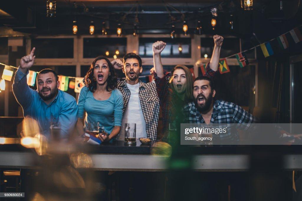 Amis, acclamant dans un pub : Photo