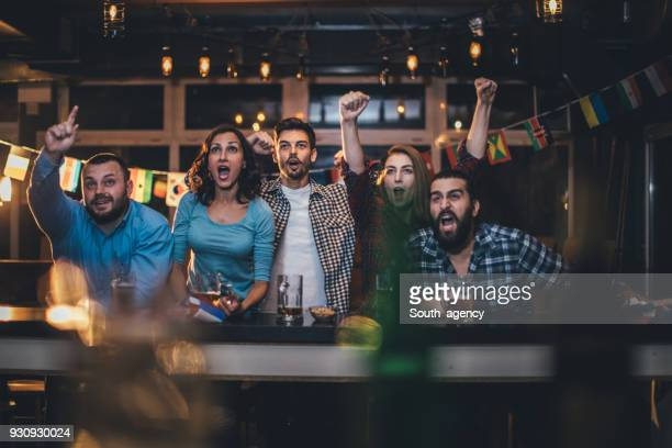 friends cheering in a pub - match sport stock pictures, royalty-free photos & images