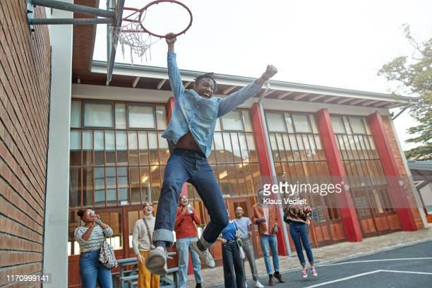 friends cheering man hanging from basketball hoop - trefferversuch stock-fotos und bilder