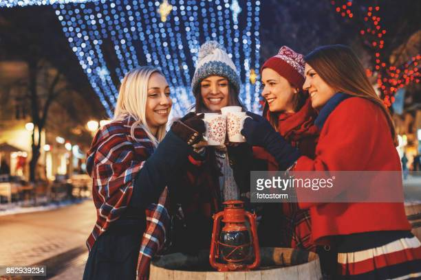 Friends cheering on a street decorated with Christmas lights