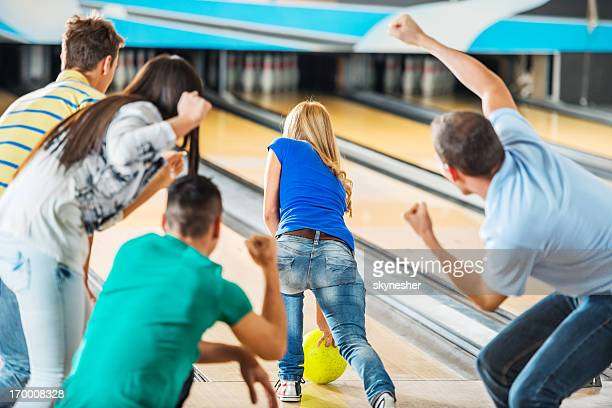 Friends cheering while girl is throwing a bowling ball.